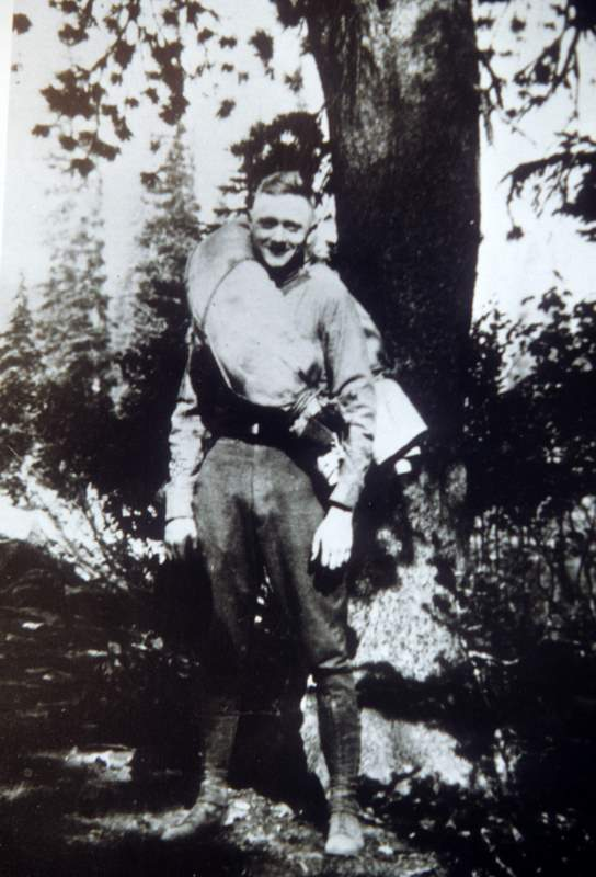 Young William O. Douglas standing next to a tree in 1914.