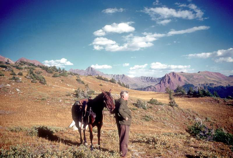 Supreme Court Justice William O. Douglas standing next to his horse in the wilderness in Aspen, Colorado in 1960.