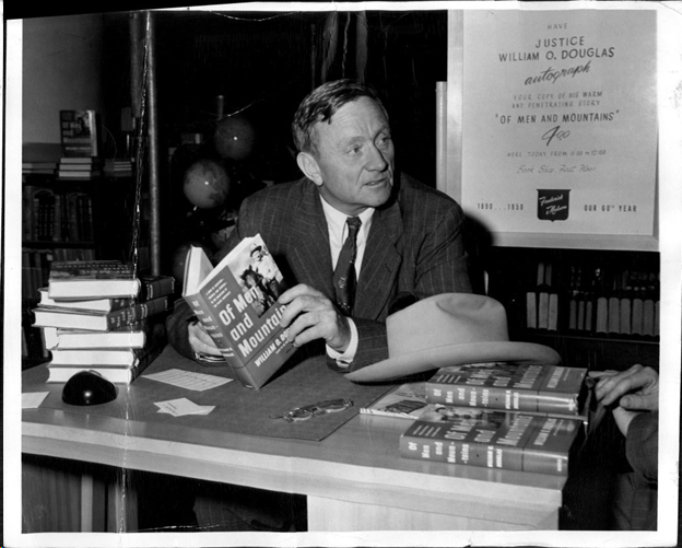 "Supreme Court Justice William O. Douglas at a book signing for his book ""Of Men and Mountains"". Black and white"