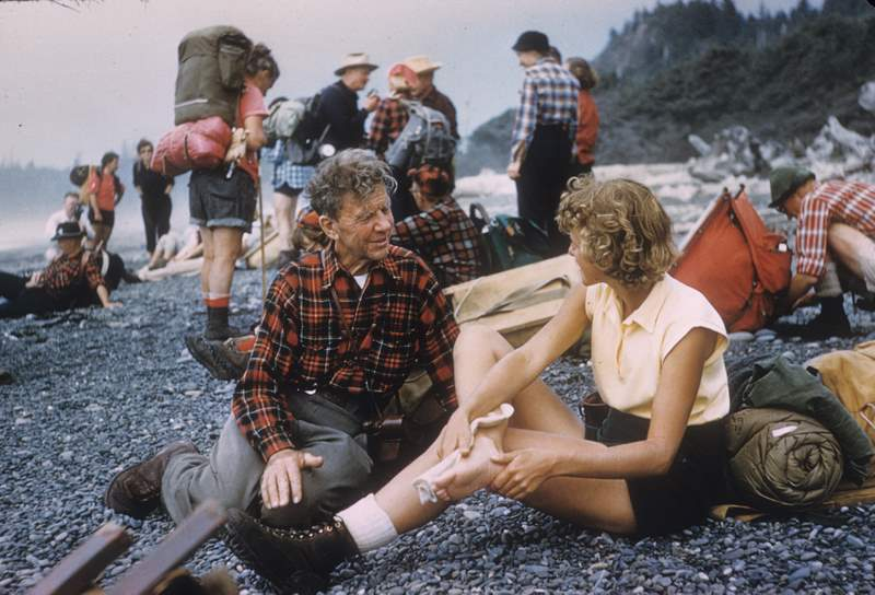 Supreme Court Justice William O. Douglas and a group of hikers at Olympic beach in Washington state. Color.